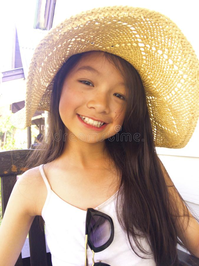 Asian long black hair girl is wearing straw hat . She is sitting stock image
