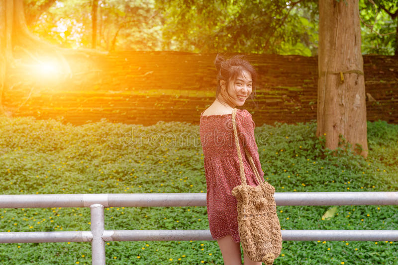 Asian long hair lady look back and big smile,dress in casual red. Short dress and bag,happy moment in sunny day at summer time stock image