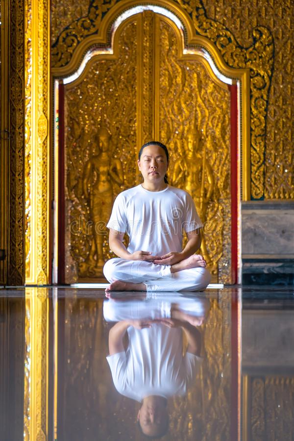 Asian long hair man relaxes meditation with all white costume sit in front of Buddist`s gold wallpaper in the Temple, Thailand. Asian long hair man relaxes stock photo