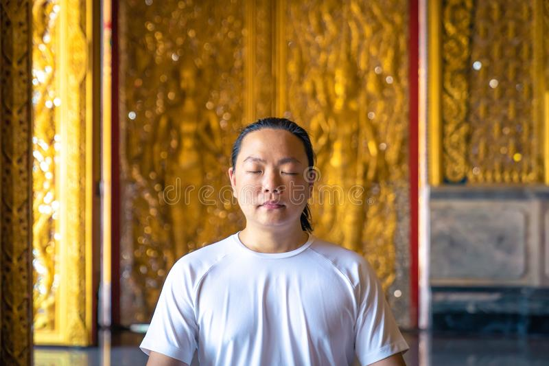 Asian long hair man relaxes meditation with all white costume sit in front of Buddist`s gold wallpaper in the Temple, Thailand. Asian long hair man relaxes royalty free stock images