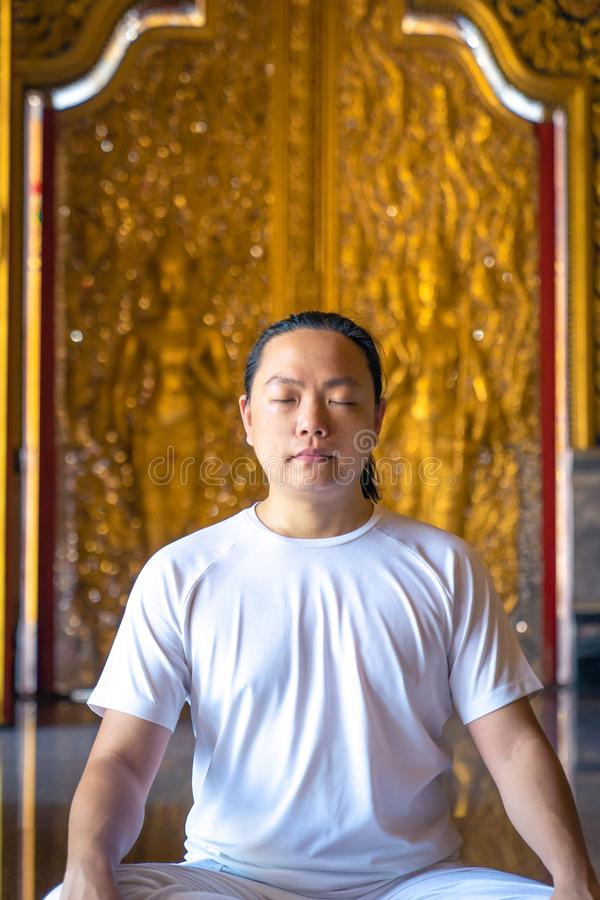 Asian long hair man relaxes meditation with all white costume sit in front of Buddist`s gold wallpaper in the Temple, Thailand. Asian long hair man relaxes stock photography