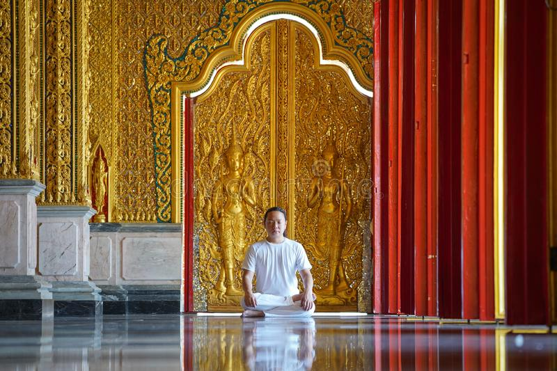 Asian long hair man relaxes meditation with all white costume sit in front of Buddist`s gold wallpaper in the Temple, Thailand. Asian long hair man relaxes stock images
