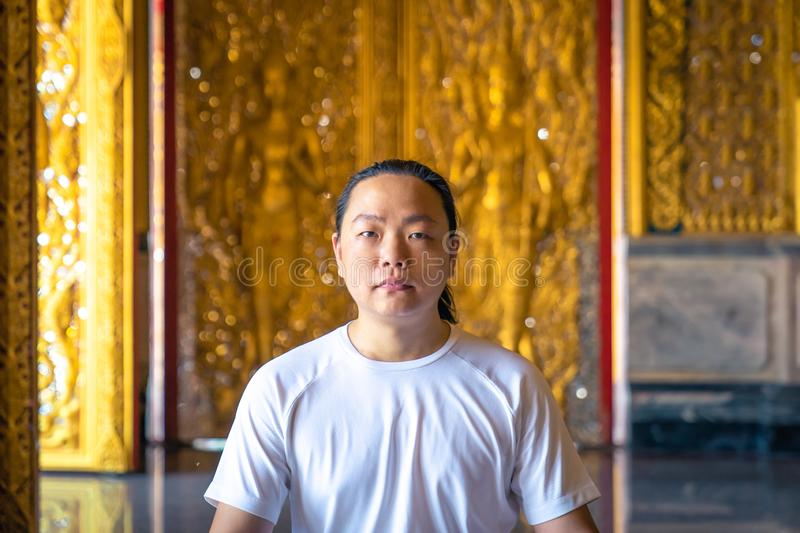 Asian long hair man relaxes meditation with all white costume sit in front of Buddist`s gold wallpaper in the Temple, Thailand. Asian long hair man relaxes royalty free stock image