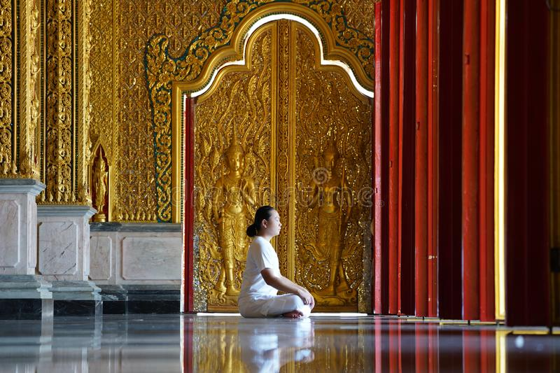 Asian long hair man relaxes meditation with all white costume sit in front of Buddist`s gold wallpaper in the Temple, Thailand. Asian long hair man relaxes royalty free stock photography