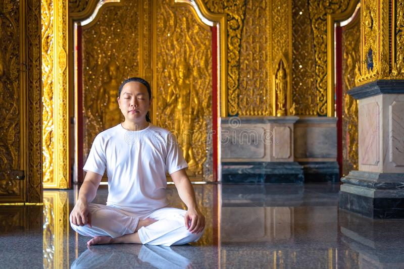 Asian long hair man relaxes meditation with all white costume sit in front of Buddist`s gold wallpaper in the Temple, Thailand. Asian long hair man relaxes stock image