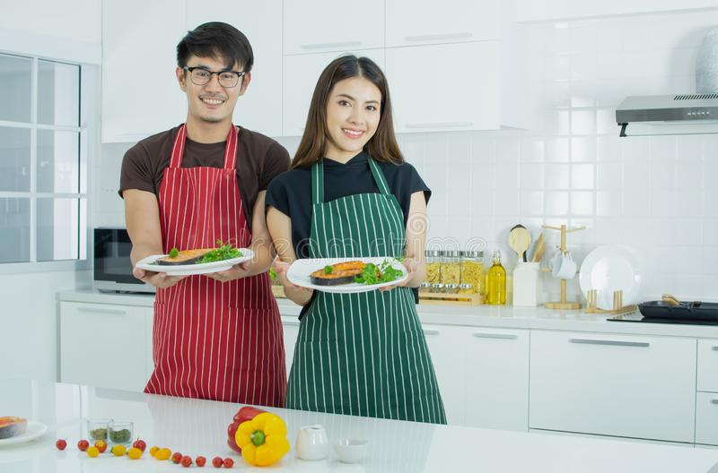 An asian lovely couple is cooking in the kitchen royalty free stock images