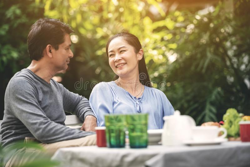 Asian lovely couple retirement having a happiness talking during dinner in backyard. Happy family after retirement.  stock images