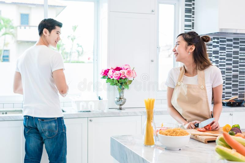 Asian lovers or couples cooking so funny together in kitchen with full of ingredient on table. Honeymoon and Happiness concept. stock images