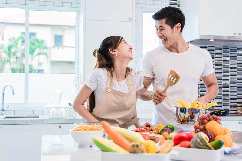 Asian lovers or couples cooking so funny together in kitchen wit. H full of ingredient on table. Honeymoon and Happiness concept. Valentines day and Sweet home stock photo