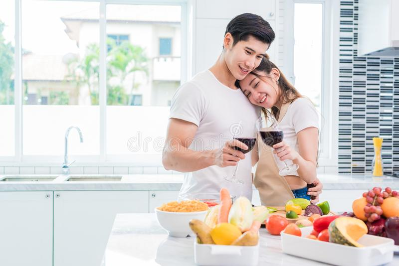 Asian lovers or couples drinking wine in kitchen room at home. L stock photography