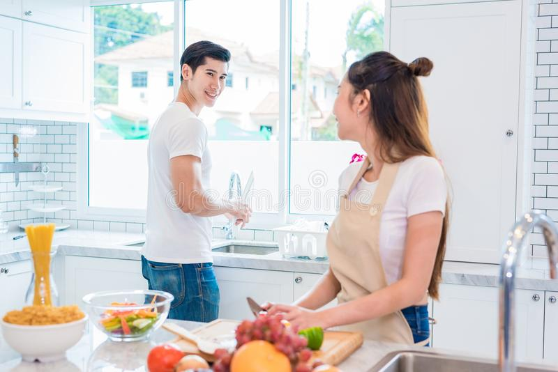 Asian lovers or couples looking each other when cooking so funny. Together in kitchen with full of ingredient on table. Honeymoon and Happiness concept stock photography