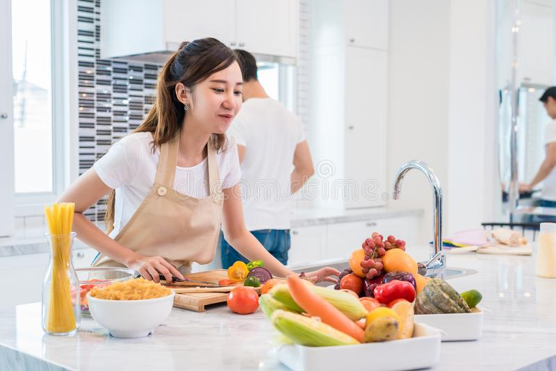 Asian lovers or couples preparing and looking for necessary ingredients in kitchen with full of ingredient on table. Honeymoon royalty free stock photos