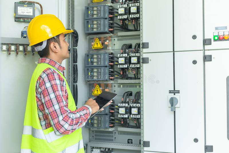 Asian maintenance engineers inspect relay protection system with royalty free stock photo