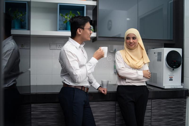 Asian malay couple having a coffee in pantry office royalty free stock photos