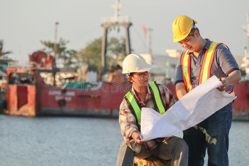 Asian male architects with blueprint working at construction site with safety stock image
