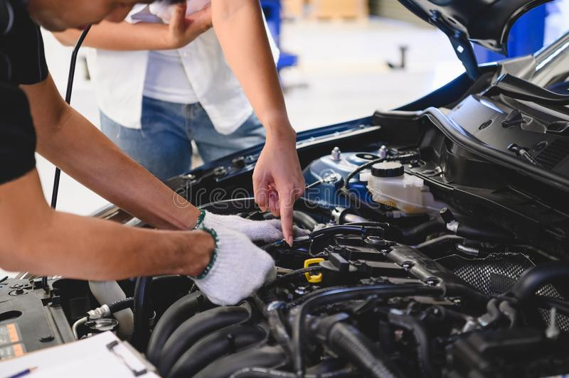 Asian male auto mechanic examine car engine breakdown problem in front of automotive vehicle car hood with female customer. Safety royalty free stock images
