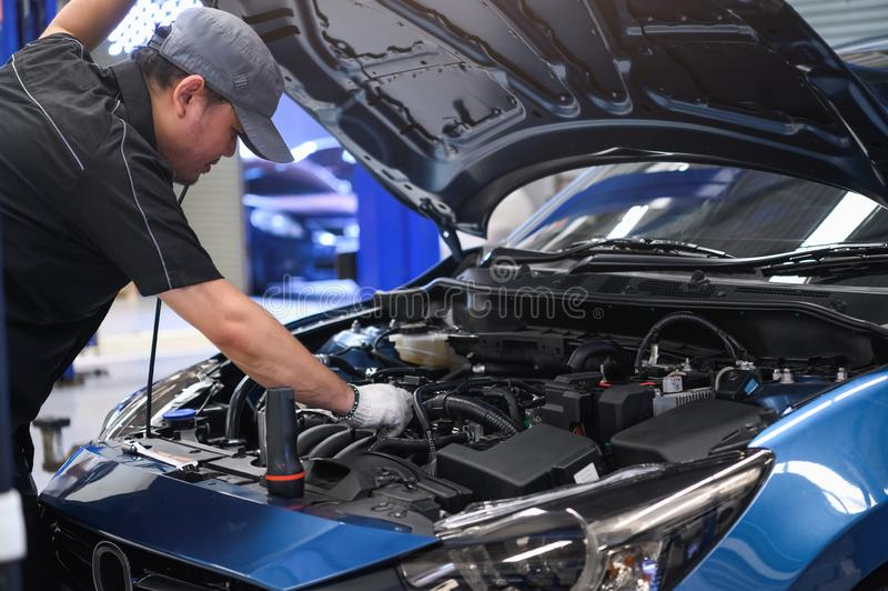 Asian male auto mechanic examine car engine breakdown problem in front of automotive vehicle car hood. Safety technical inspection. Care check service stock photo
