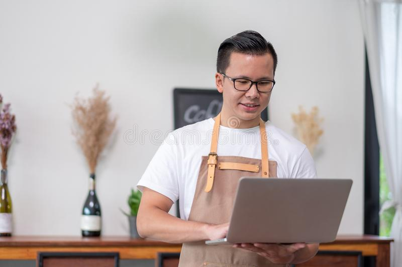 Asian male Barista cafe owner using laptop checking stock business inside coffee shop, food and drink business start up royalty free stock image