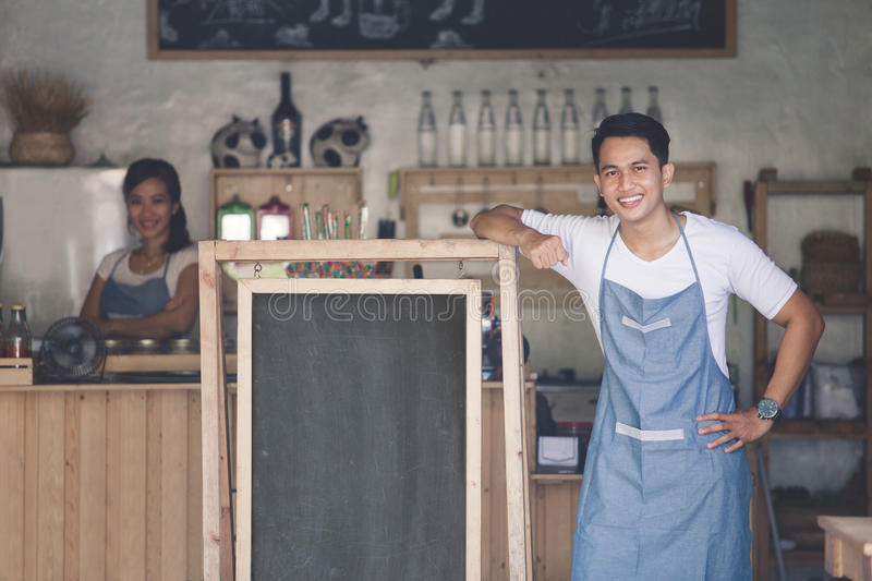 Asian male cafe owner with blank board royalty free stock photo
