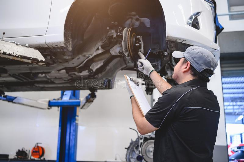 Asian male car technician car maintenance for customers according to specified vehicle maintenance checklist. Disk brake pad wear royalty free stock photo