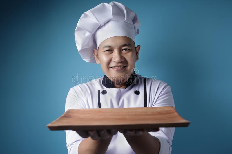Asian Male Chef Shows Empty Wooden Plate, Presenting Something, Copy Space royalty free stock photos