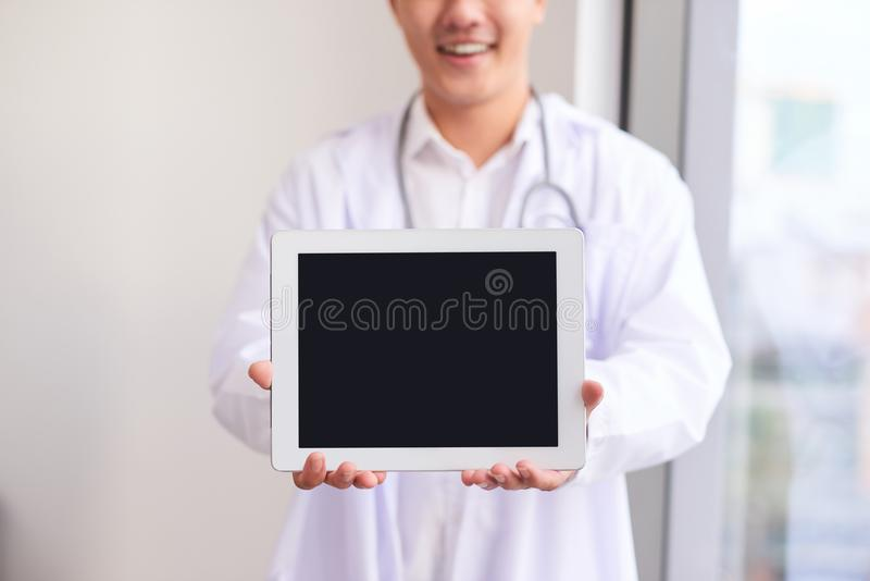 Asian male doctor shows his blank screen of computer tablet, close up royalty free stock photography