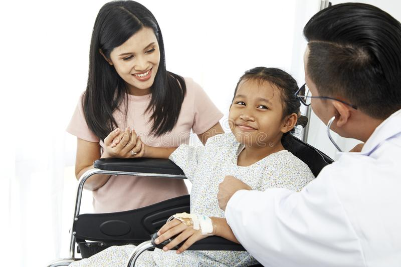 Asian male doctor talking to young child stock photography