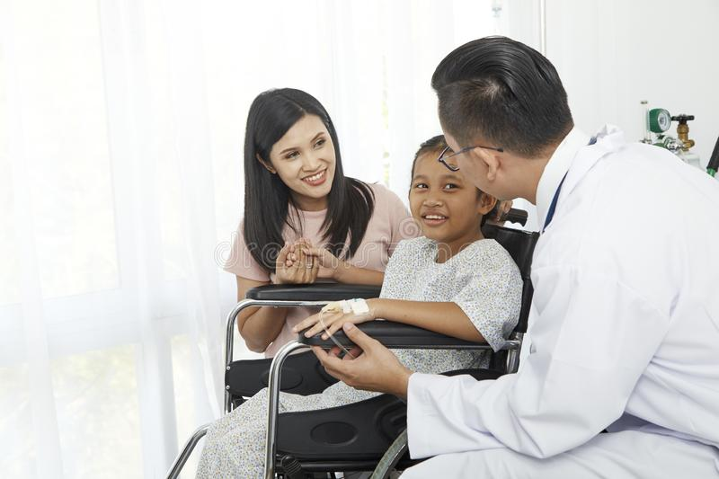 Asian male doctor talking to young child stock image