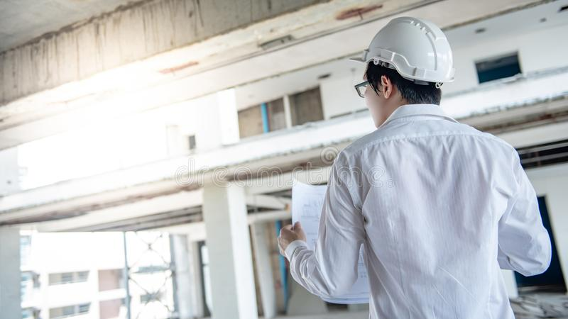 Asian male engineer checking blueprints at construction site stock photography