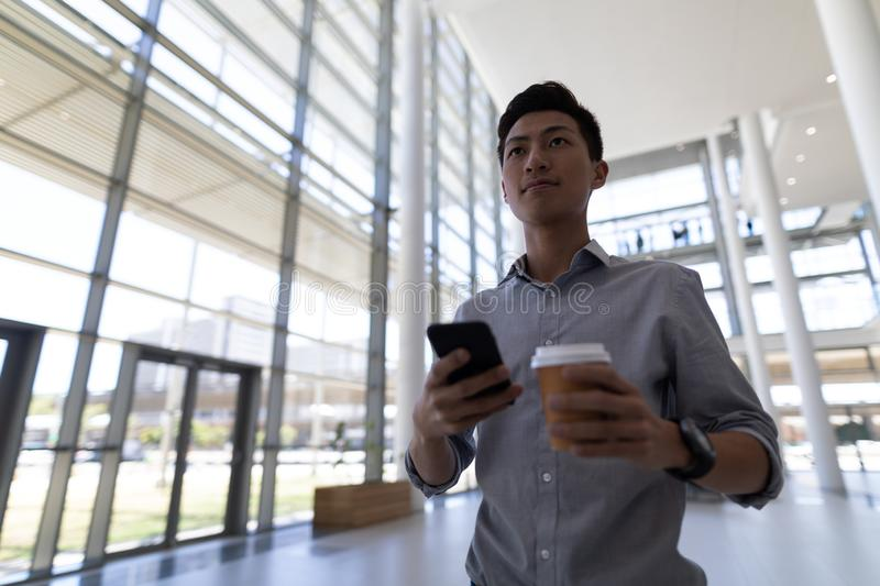 Asian male executive having coffee while using mobile phone in modern office stock images