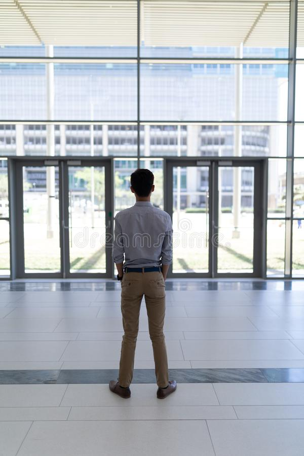 Asian male executive standing in modern office stock photography