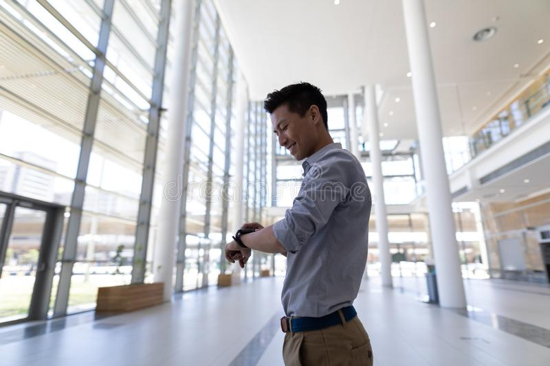 Asian male executive using smartwatch in modern office royalty free stock photos