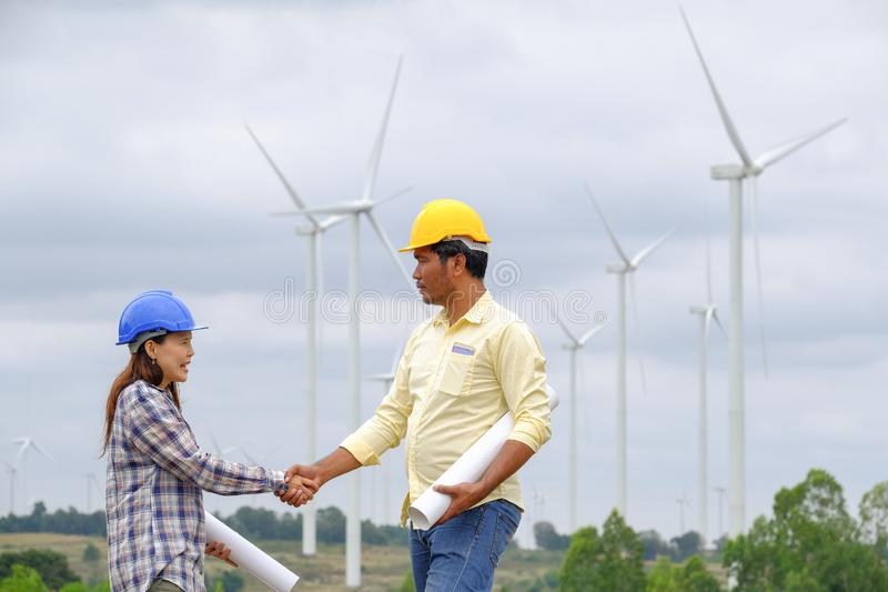 Asian male and female engineers are planning develop wind power stock images