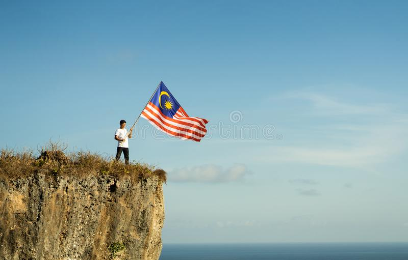 Asian male with indonesian flag celebrating independence day. Proud indonesian man on a beach cliff raising red and white indonesia flag stock images
