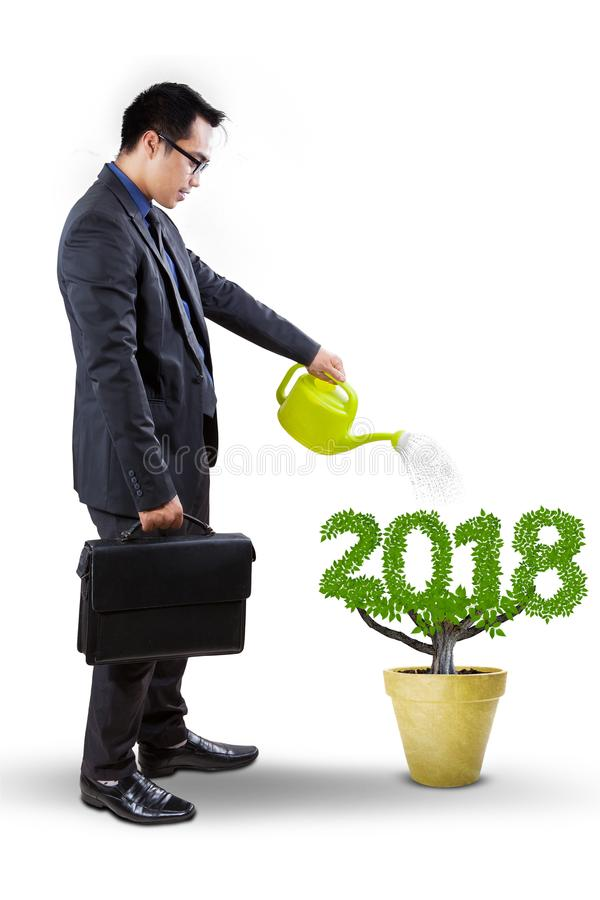 Male manager watering a plant on studio. Asian male manager watering a plant shaped number 2018 in the pot, isolated on white background stock photos
