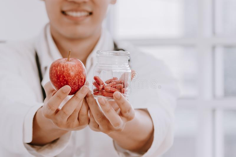 Asian male nutritionists hold red apples royalty free stock photo