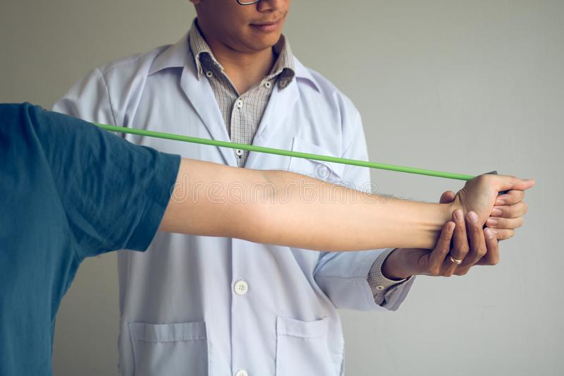 Asian male physical therapist descent working and helping to protect the hands of patients with patient doing stretching exercise stock image