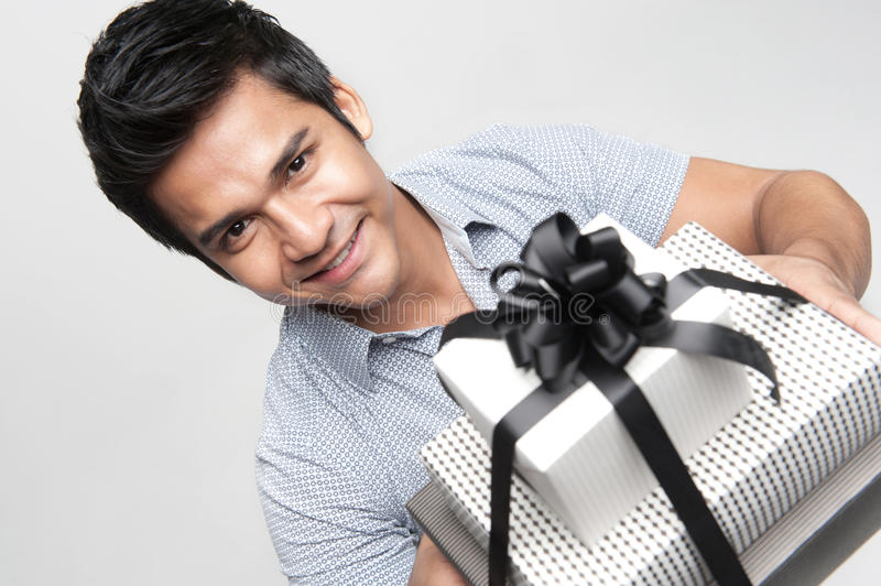 Asian male presenting gift royalty free stock photography