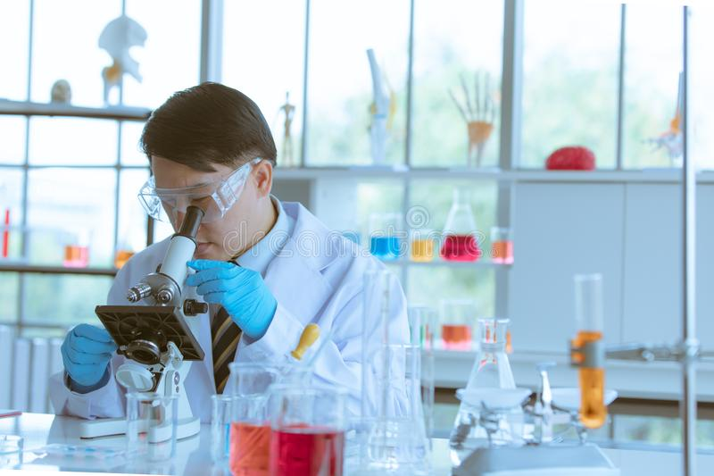 Scientist adjusting microscope for experiment royalty free stock photos