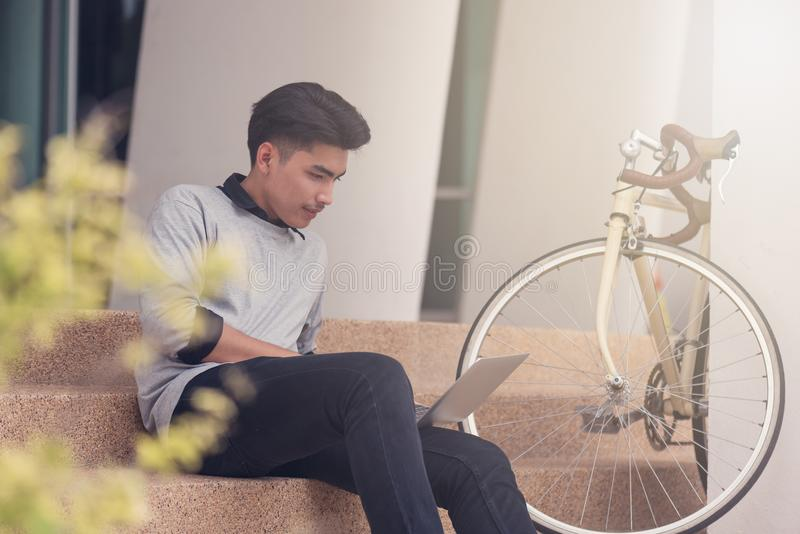 Asian male student sitting at the stairs and smiling as use laptop computer with his bike background at campus,Students and royalty free stock photography