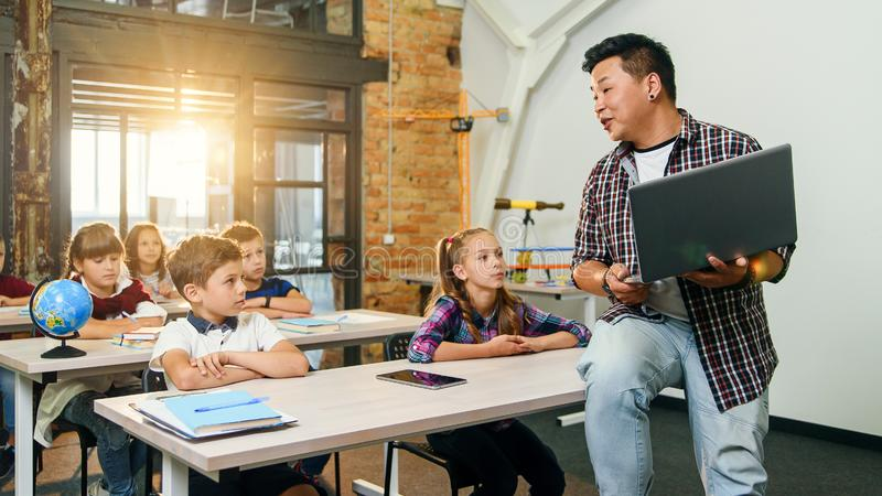 Asian male teacher sits on desk with laptop in hands and explaining lesson for six elementary school pupils. School stock photos