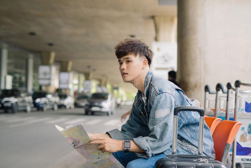 Asian male tourist reading map while waiting for taxi on bus stop with suitcases.  royalty free stock photography
