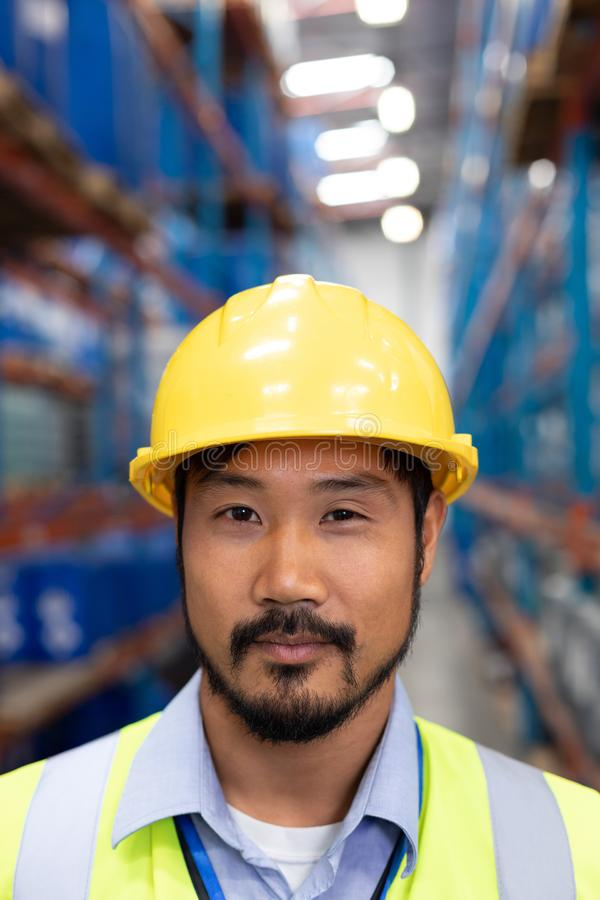 Asian male worker looking at camera in warehouse royalty free stock photography