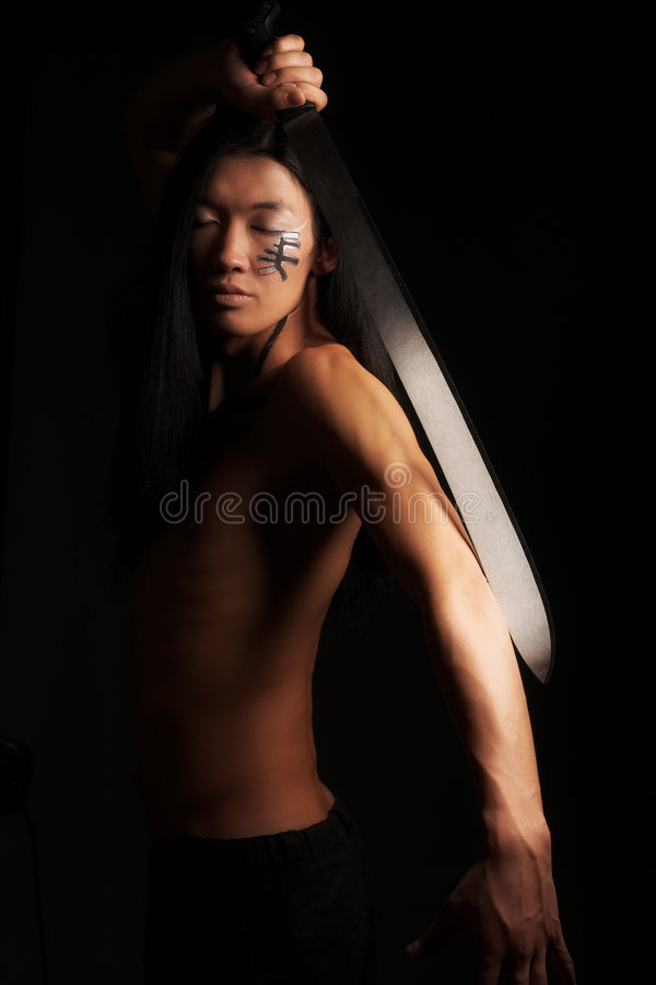 Asian man. Studio portrait of an asian man with katana royalty free stock images