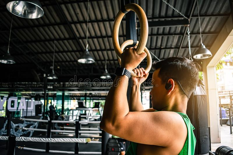 Asian man athlete gymnast rings exercise in gymnastics exercise stock photo