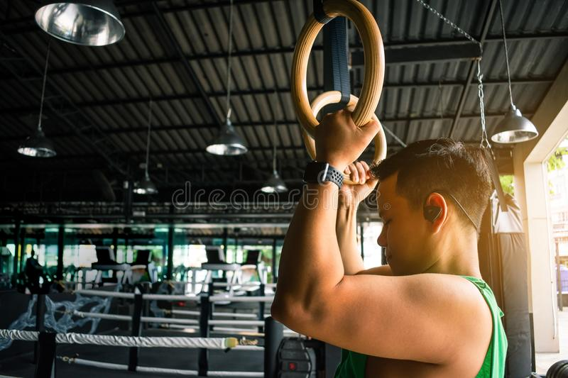 Asian man athlete gymnast rings exercise in gymnastics exercise stock photography