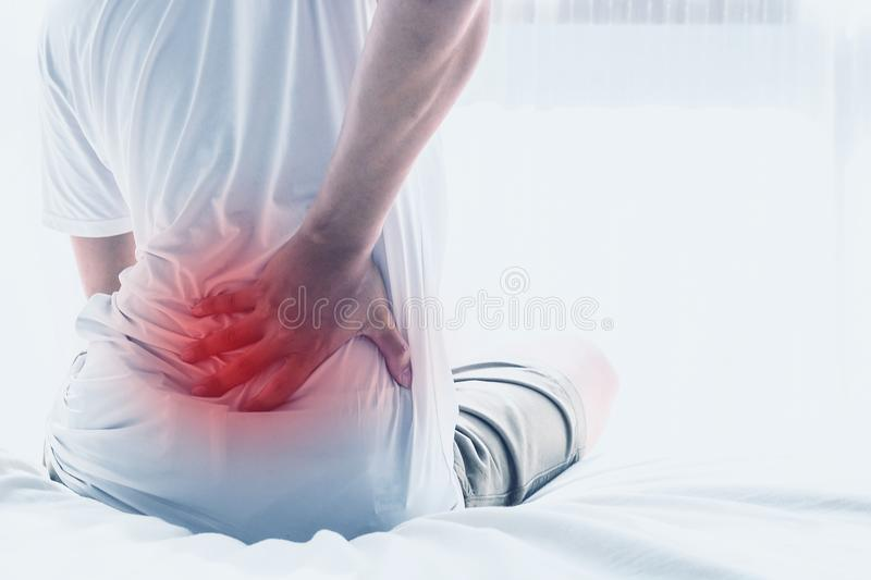 Asian man back pain and sit on bed in bedroom. In the morning.color tone royalty free stock images