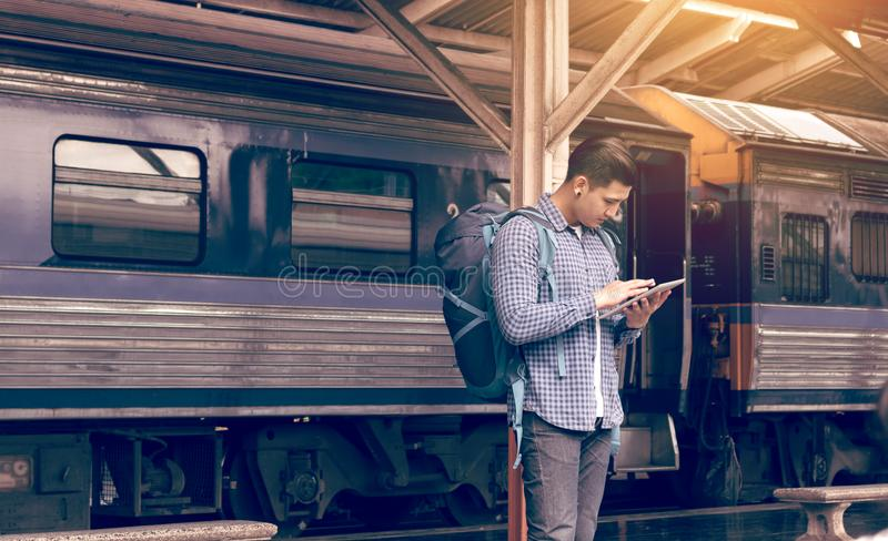 Asian man backpack for travel at train station and using tablet stock photography