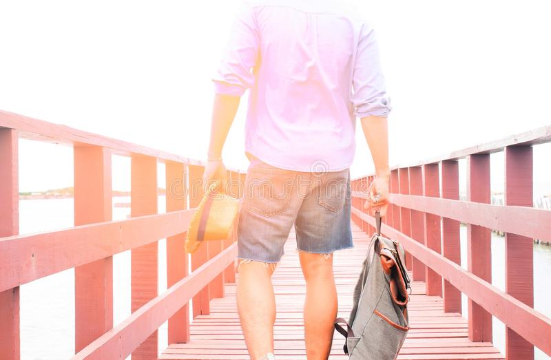 Asian man with backpack traveling on bridge to the sea, Summer travel royalty free stock photos