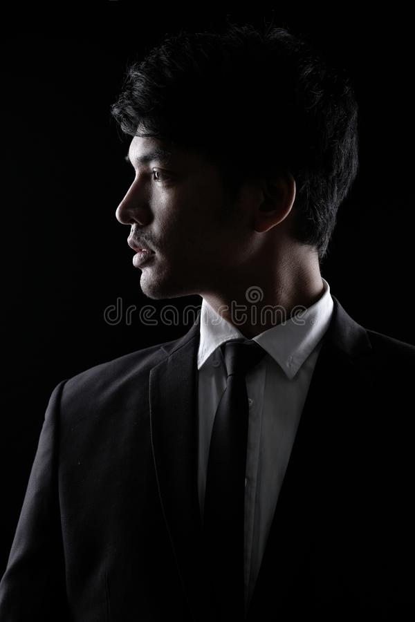 Asian man in black formal suit in the dark royalty free stock photo
